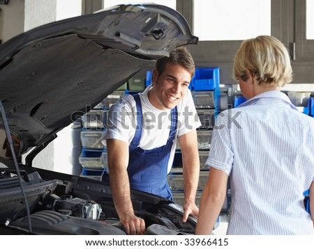 mechanic talking with female client in auto repair shop. - stock photo