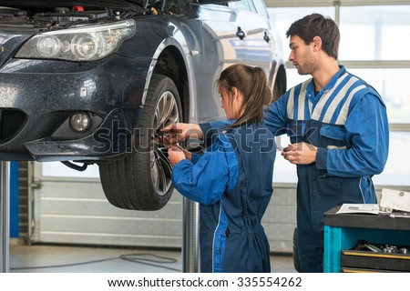 Mechanic teaching an intern the best practice. Learning on the job during a practical internship in a garage - stock photo