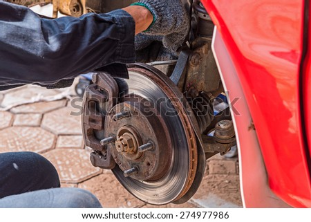 Mechanic technician worked replacing brakes vehicle of automobile at repair service station.  - stock photo
