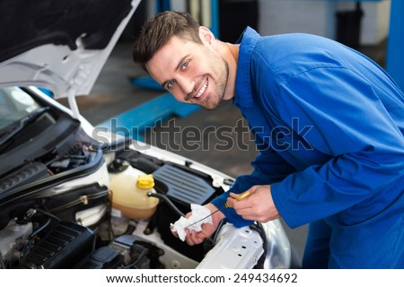 Mechanic testing oil in car at the repair garage - stock photo