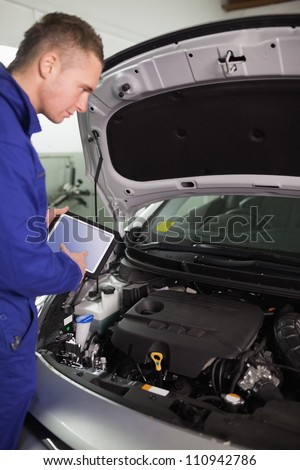 Mechanic testing the engine with a tablet computer in a garage