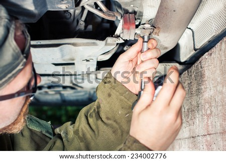 Mechanic Tightening Tailpipe Under a Car