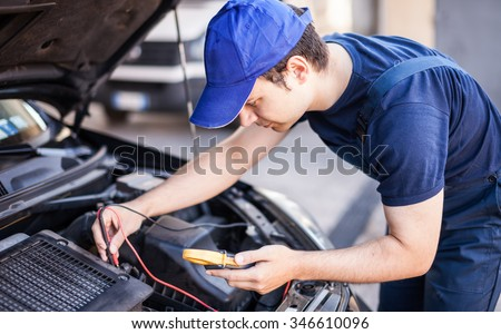Mechanic troubleshooting a car engine - stock photo