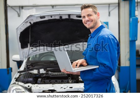 Mechanic typing on a laptop at the repair garage - stock photo