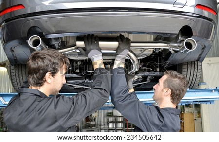 Mechanic Under Car Installing Exhaust Pipe. New generation of sportive mufflers: double Car Exhaust Pipe chromed made of stainless steel - stock photo