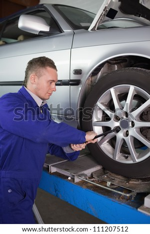 Mechanic unscrewing a bolt with a wrench in a garage