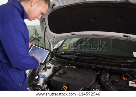 Mechanic using a tablet computer in a garage