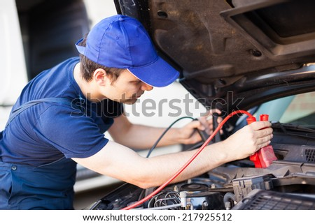 Mechanic using booster cables to start-up a car engine - stock photo