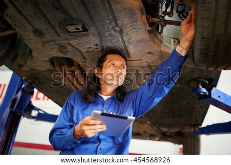 Mechanic using tablet computer when checking car - stock photo