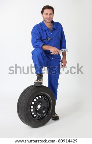 Mechanic with a spare tyre - stock photo