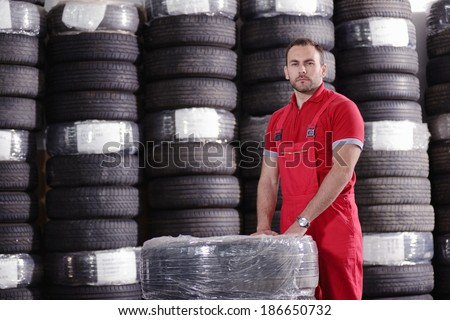 mechanic with car tires - stock photo