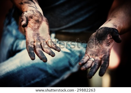 mechanic with dirty hands after fixing the brakes - stock photo