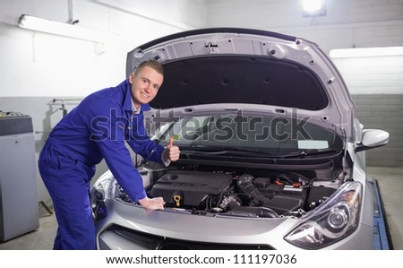 Mechanic with his thumb up in a garage