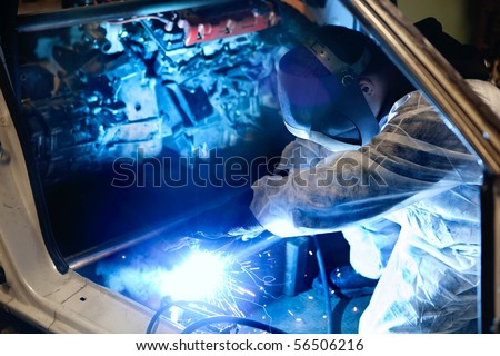 mechanic with protective mask welding car body - stock photo