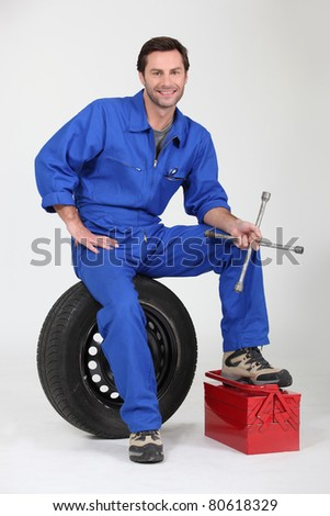 Mechanic with spare wheel and tool box - stock photo