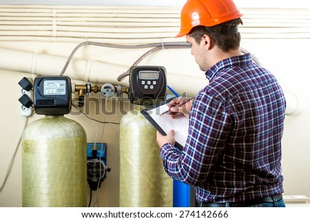 Mechanic worker checking work of industrial equipment on factory - stock photo