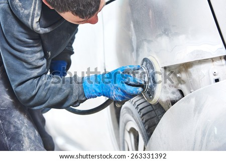 mechanic worker repairman sanding polishing car body and preparing automobile for painting during repair and renew at service station shop  - stock photo