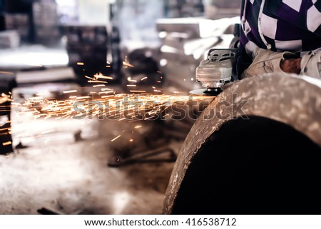 mechanic worker using grinder for polishing an iron block - stock photo