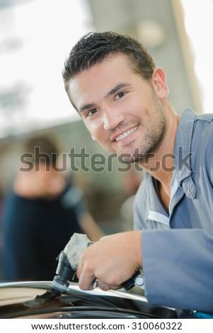 Mechanic working in a garage - stock photo