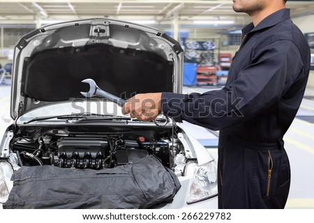 mechanic working in auto repair shop with a wrench for inspector - stock photo