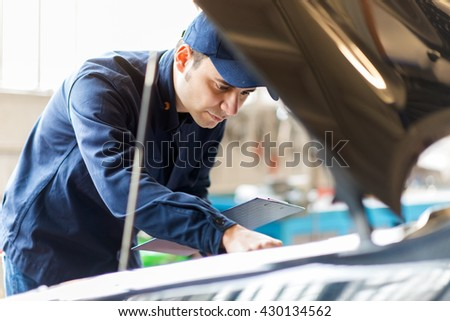 Mechanic working in his workshop - stock photo