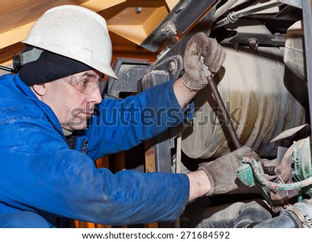 Mechanic working on a broken vehicle, transmission repair - stock photo