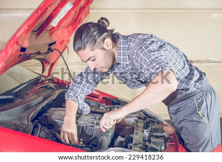 mechanic working on a red car. concept about transportation,people and industry - stock photo