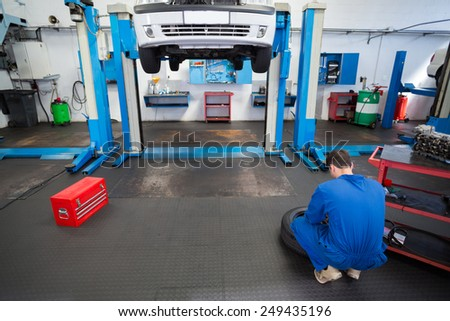 Mechanic working on a tire wheel at the repair garage - stock photo