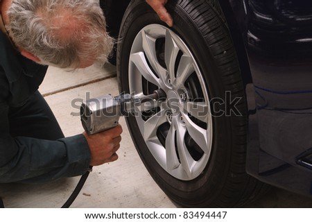 Mechanic working on car using an air impact tool to change tires on a vehicle. - stock photo
