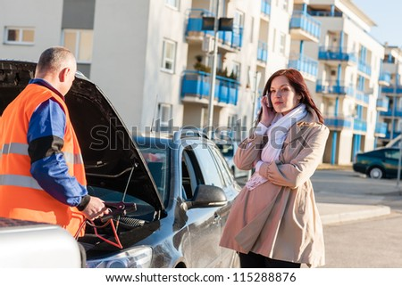 Mechanic working on woman's car after breakdown phone calling problem - stock photo
