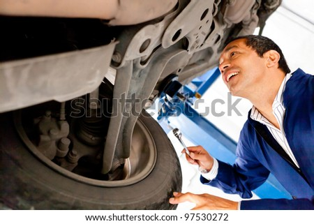 Mechanic working under a car at a repair shop - stock photo
