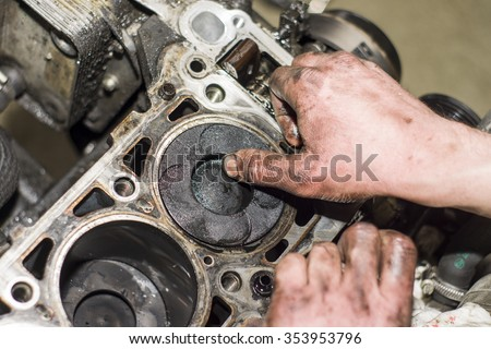 Mechanic working with with engine in a workshop