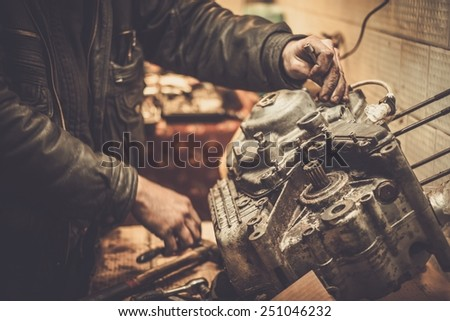 Mechanic working with with motorcycle engine in a workshop - stock photo