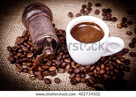 Mechanical antique coffee grinder, cup of coffee. - stock photo