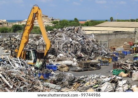 Mechanical crane grabber working in a scrapyard - stock photo