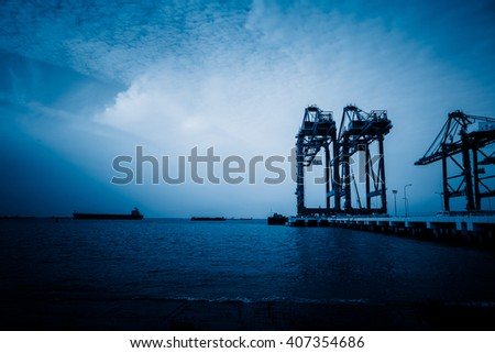 mechanical cranes lifting freight at pier,blue toned image. - stock photo