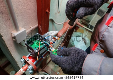 Mechanical engineer installs control devices for central heating systems in modern boiler room, hands with tool close-up.