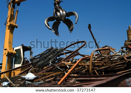 Mechanical grabber working in a scrapyard - stock photo