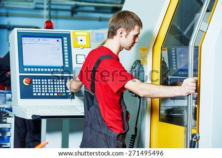 mechanical industrial worker at cnc milling machine center in tool manufacture workshop - stock photo