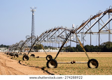 Mechanical irrigation system on recently planted farm - stock photo