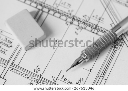 Mechanical pencil and eraser on technical drawing, construction plan