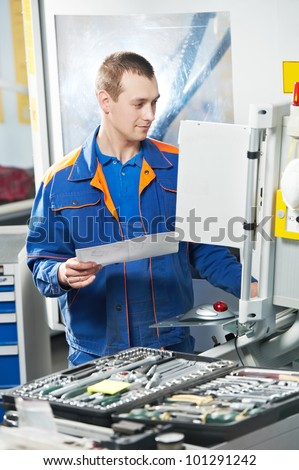 mechanical technician laborer working on modern cnc metal machining milling center in tool manufacturing workshop - stock photo