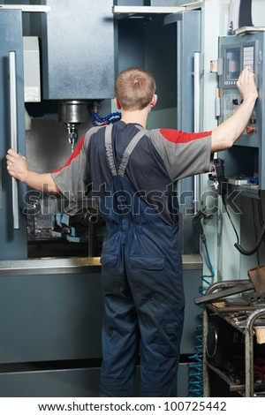 mechanical technician worker at metal machining milling center in tool workshop - stock photo