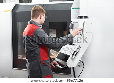 mechanical technician worker at modern cnc metal machining milling center in tool workshop - stock photo