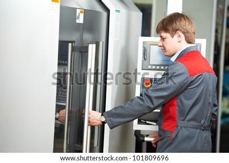 mechanical technician worker near modern cnc metal machining milling center in tool workshop - stock photo