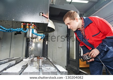 mechanical technician worker of cnc milling cutting machine center at tool workshop manufacturing - stock photo
