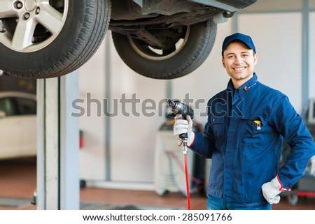 Mechanician changing car wheel in auto repair shop - stock photo