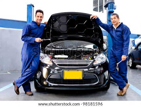 Mechanics at a car repair shop fixing an engine - stock photo