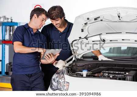 Mechanics Discussing While Using Tablet Computer By Car - stock photo