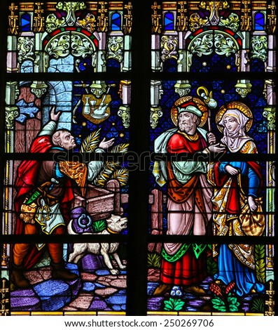 MECHELEN, BELGIUM - JANUARY 31, 2015: Stained Glass window depicting Joseph and Mother Mary refused refuge in a tavern in Bethlehem, in the Cathedral of Saint Rumbold in Mechelen, Belgium. - stock photo